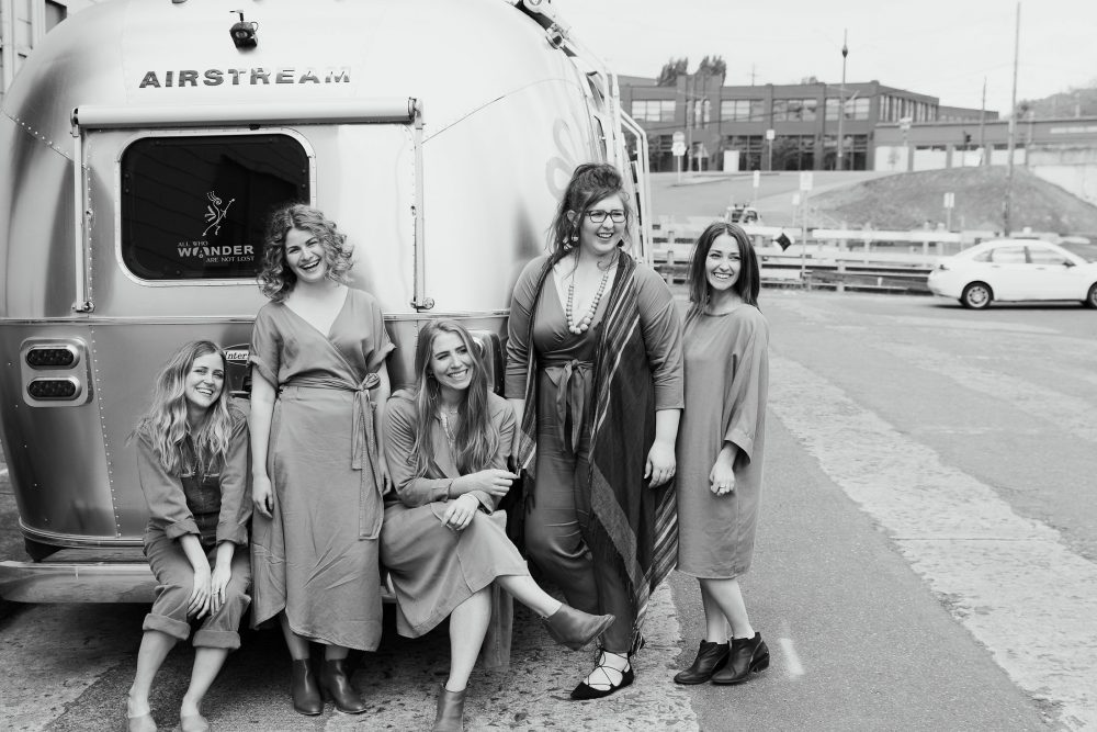 The Yellow Co. girls stand in front of their Airstream